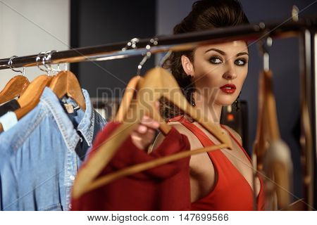 Pretty young woman is choosing clothing for fitting. She is standing and looking at dress with desire