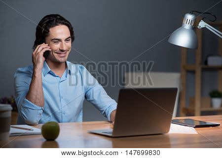 Pleasant telephone conversation. Handsome happy young man smiling and sitting at the table while having conversation on cellphone.