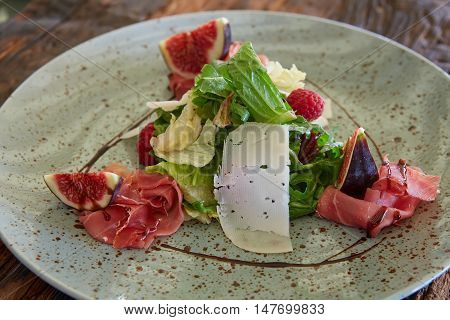 Fresh salad with figs, prosciutto and goat cheese.