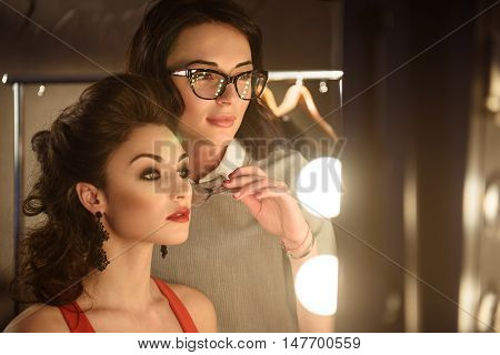 Talented stylist is applying blush on female cheek with inspiration. She is standing near model and looking at mirror with concentration