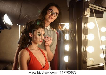 Elegant young woman is getting facial make-up backstage. She is sitting and looking at mirror with confidence. Joyful beautician is holding brush and smiling