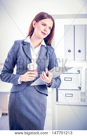 Attractive young businesswoman standing near desk with folder in the office
