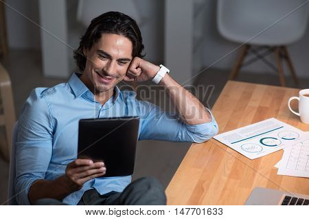 Such an interesting work. Handsome involved young man sitting at the table and smiling while working on tablet.
