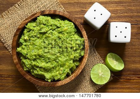 Avocado dip or guacamole in wooden bowl photographed overhead with natural light (Selective Focus Focus on the avocado dip)