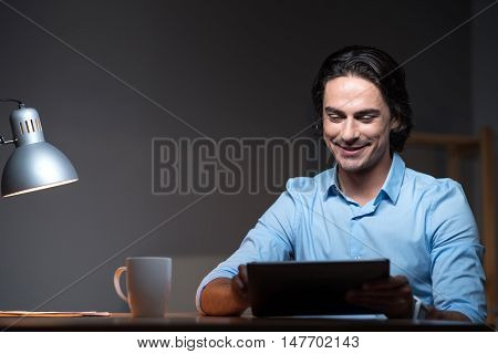 Night work . Handsome enthusiastic young man sitting at the table and smiling while using tablet.
