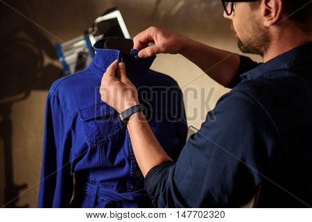 Skillful fashion designer is adjusting dress on mannequin. Man is standing backstage and looking at cloth with inspiration
