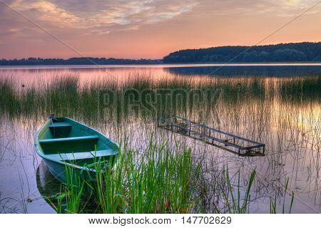 Rowing boat floating over the Lake Lasmiady waters. Masuria Poland. HDR image