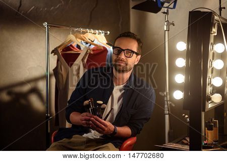 Talented stylist is working in dressing room. He is sitting on chair and showing set of make-up brushes. Man is looking at camera with confidence. Clothing hanging on background