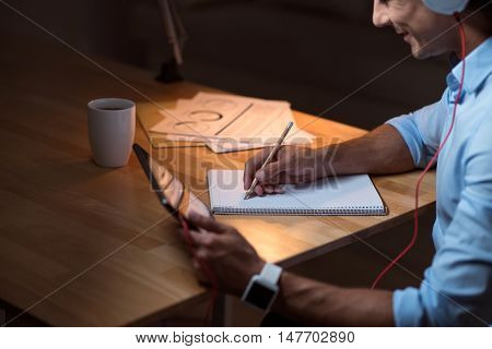 Involved in work. Joyful young man writing in the note book and holding tablet while sitting at the table.
