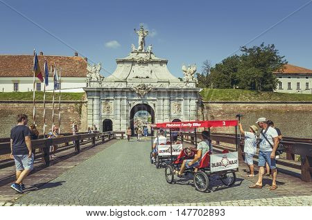 Alba Iulia, Romania - July 24, 2016: Tourists riding rented four wheels bicycles enter the third gate of Alba Carolina Citadel the largest gate of the fortress.