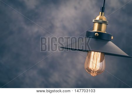 Retro light lamp with Edison light bulb at right of blurred background.Toned