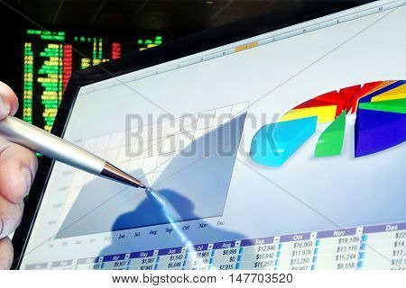 Man Analyzing Financial Data and Charts on Computer Screen