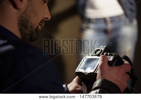 Male photographer is looking at photos in camera with satisfaction. Woman is posing on background in studio