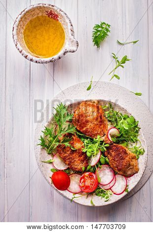 Roasted pork medallions on watercress with radishes top view