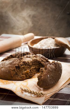 Cracked rough rye rural bread on table still-life
