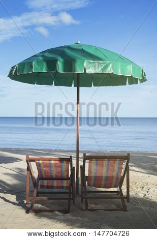 two Beach chairs and umbrella on the beach with blue sky and blue sea view in background at sunset moment,selective focus,filtered image