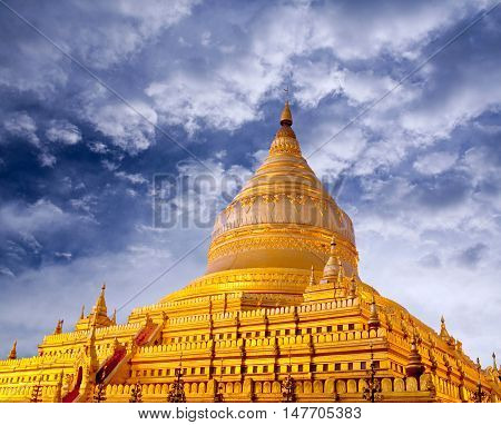 Golden Shwezigon Pagoda at sunrise in Bagan, Myanmar. Construction of the Shwezigon Pagoda began during the reign of King Anawrahta and was completed in 1102 AD during the reign of King Kyansittha of the Pagan Dynasty.