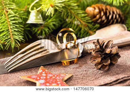 Silverware on napkin among Christmas decorations closeup