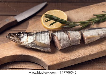 Sliced smoked fish on cutting board and lemon