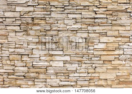 Rock stone brick tile wall aged texture detailed pattern background in light yellow cream brown color tone/ancient rustic limestone patterned backdrop for decoration in beige toned colour