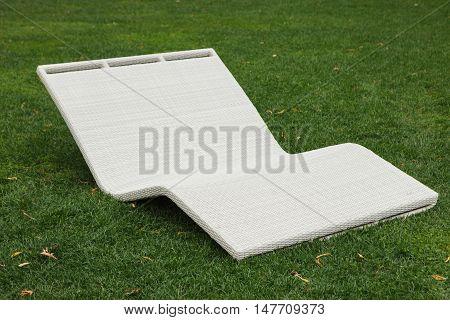 White resort cane-chair recliner or sunbed. Lay down under the sun and relax. Good place for relaxation and sunbathing. Daybed on green grass