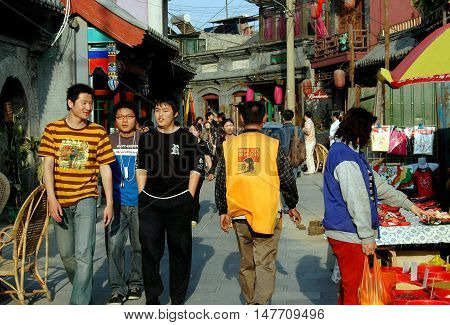 Beijing China- May 5 2005: People walking along a busy street in the Shi Sa Hai Hutong lined with homes and shops