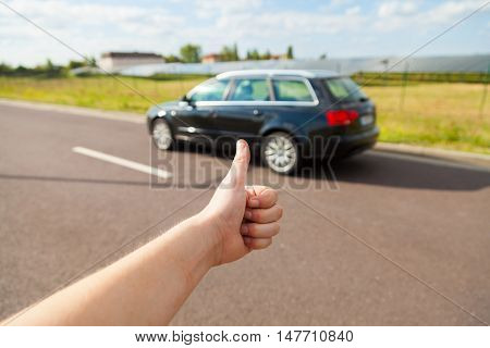 new car with a human hand thumbs up