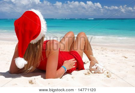 Woman on the beach in santa's hat