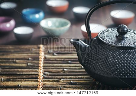 Traditional oriental iron teapot and teacups on bamboo placemat with copy space