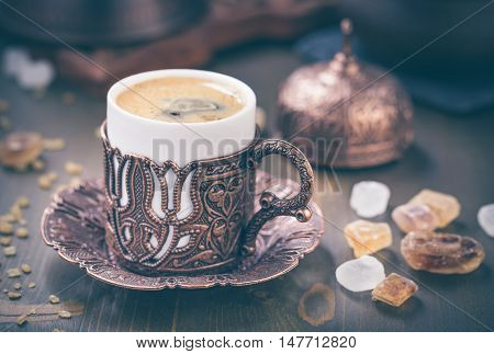 Turkish embossed metal coffee cup on table. Toned