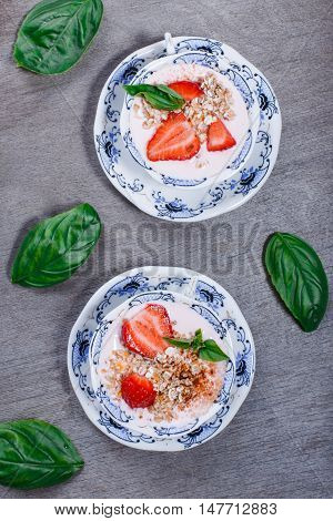 Healthy cereal with strawberries and yogurt decorate with mint in a ceramic bowls on wooden table top view. Granola muesli