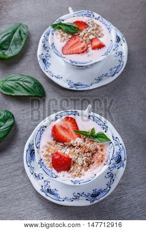 Granola muesli with strawberries and yogurt decorate with mint in a ceramic bowls on wood grey background. Healthy breakfast