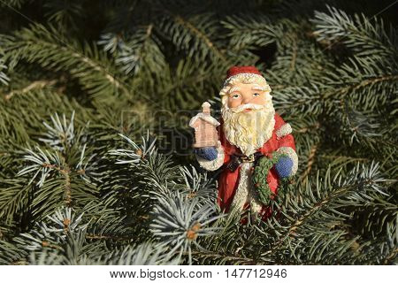 Christmas and New Year's toy in the form of Santa Claus. The toy is located on a fir-tree. Santa Claus in red clothes. It holds gifts