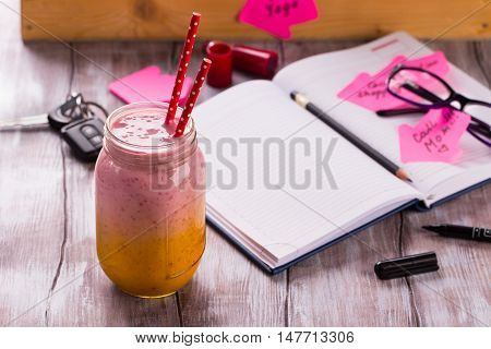 Healthy smoothie with business accessories. Young lady to do list for the day. Daily planner, glasses, pen, car keys and memory stickers on wooden table.