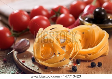 Uncooked fettuccine pasta with tomatoes on wooden board. Closeup