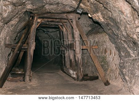 Old derelict mine into rock. Tunnel underground entrance