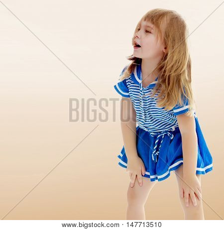 Girl enjoys the autumn weather. On a brown background.Cute little unkempt girl in a short blue dress. Girl looking to the side with his hands on his knees.