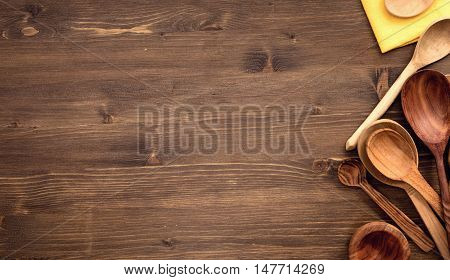 Various wooden spoons at right side of wooden table background