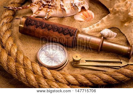 Compass with spyglass and rope on sand background