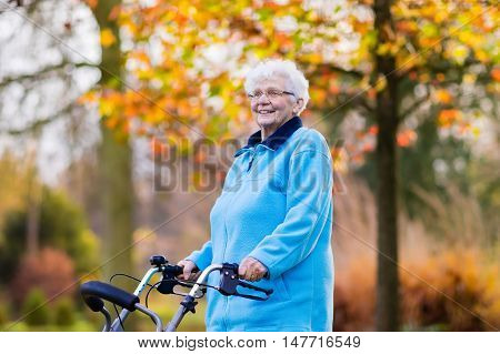 Happy senior handicapped lady with a walking disability enjoying a walk in an autumn park pushing her walker or wheel chair. Aid and support during retirement. Patient of nursing home or care center.