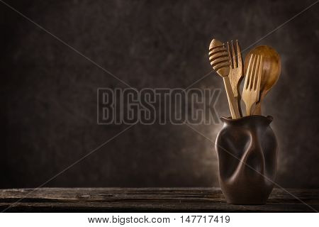 Wooden cutlery set on dark background with copy space