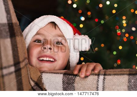 Happy child girl in a Christmas hat waiting for a miracle