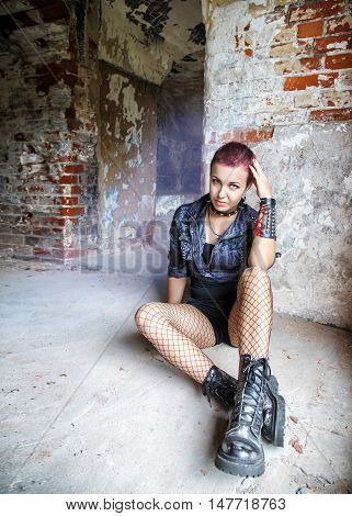 punk girl sitting on the floor in an old abandoned house