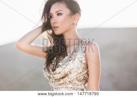 Professional photo shoot in a desert. Beautiful sexy asian woman model in luxury shiny dress in a desert