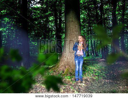 frightened little girl in denim costume standing near the tree in the dark woods