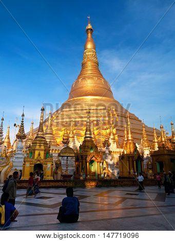YANGON, MYANMAR - JANUARY 3, 2011: Pilgrims walking around Shwedagon Pagoda.