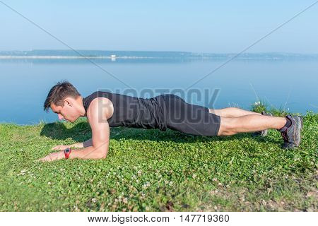 Fit man doing plank core exercise working on abdominal back muscles.