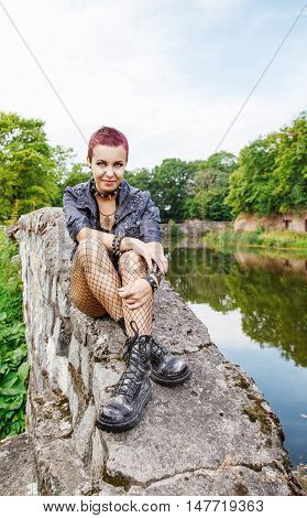 punk girl sitting on the dike near the lake outdoor