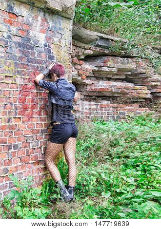 punk girl standing near the wall of hte abandoned castle outdoor