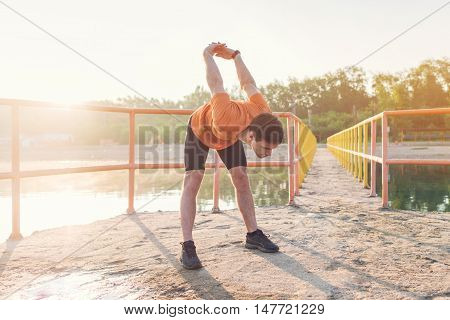 Young athlete holding his arms behind back and stretching outdoors.